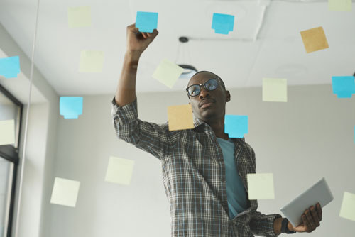 Male writing on post it notes stuck to a glass wall